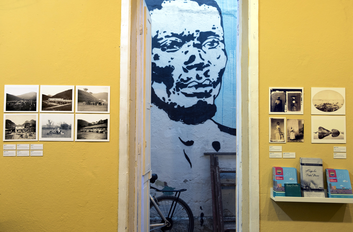 Wall facing the Black Heroine Mural in the library of the Instituto de Pretos Novos. On the foreground, reference photographs from the Instituto Moreira Salles used in the exhibition. On the background, a stencil graffiti art of a famous photograph of an enslaved man.